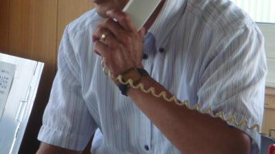 電話応対中の 建材店長カッパ